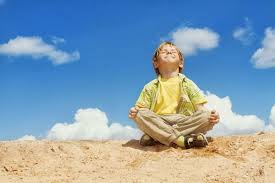 little boy meditating on top of the world